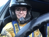 Female rally driver smiling in seat of car with helmet on