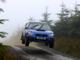 Blue subaru impreza flying in the air over crest of hill in forest rally experience